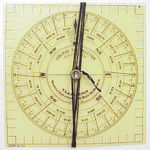 """Transparent Course Protractor.  Used with ship charts to calculate a ship's course, bearing and position.   Instead in place of a ruler.  The sailor places the center of the protractor over  the ship's position on the chart.  The silk cord and """"hands"""" are then used to complete the  calculations."""