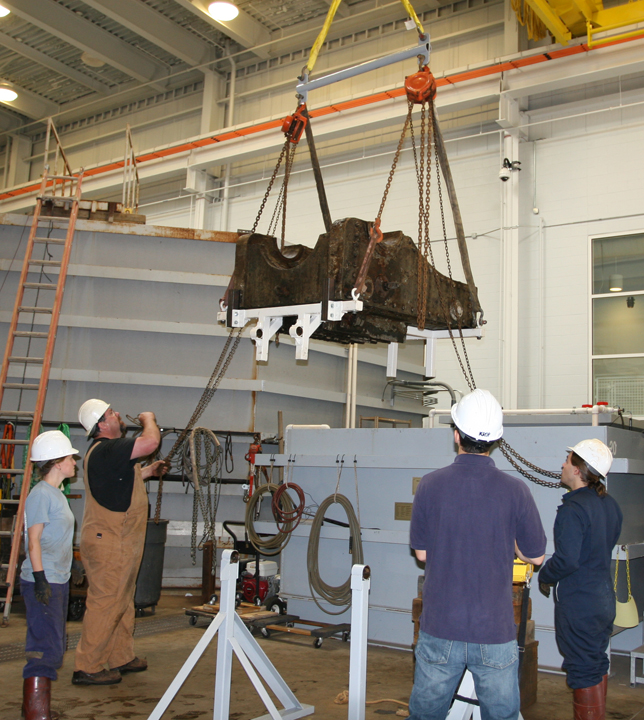 The same carriage, after rotation, is affixed to chain hoists and a spreader bar supported by the lab's overhead crane.