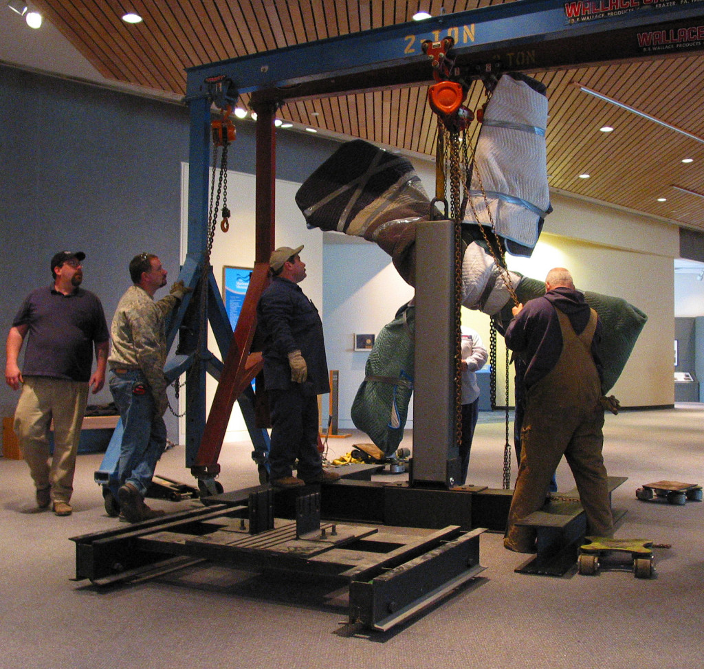 Conservation staff and rigging professionals prepare to move USS Monitor's 9-foot diameter cast iron propeller from its former location in the lobby of The Mariners' Museum to its current location within the USS Monitor Center at The Mariners' Museum.