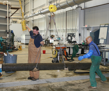 Conservation staff use a 5-ton auxiliary hoist with lifting cables to move a 10-foot long section of wrought iron propeller shaft weighing 1,900 pounds.  The shaft's surface is protected from the steel lifting cables by rubber, foam, and canvas.