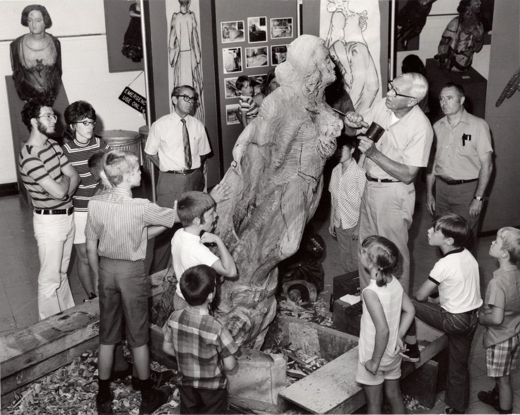 1974, Staff members carving a figurehead out of Cypress