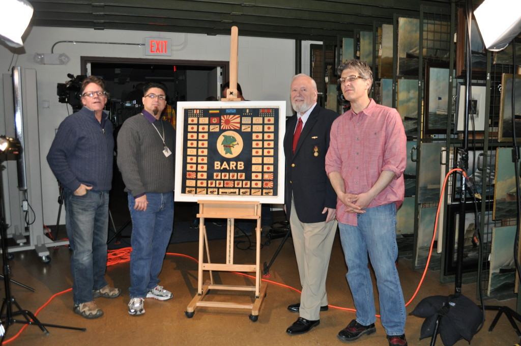 Director Rob Kerr,  museum curator Mark Nucup,  museum docent Ted Crossland, and host Geoff Edgers pose for a shot in the paintings storage room with the USS BARB (SS220) Presentation Battle Flag on 4/3/14.