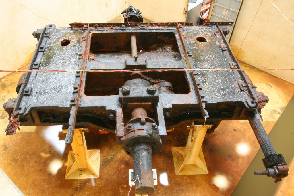 This picture shows the original bottom of USS Monitor's engine support bed. This massive casting supported the engine and rested above a series of wrought iron cross-braces or supports. Note the two similar round holes in the engine bed. Navy divers created these in order to effectively secure the engine to its custom-built recovery rig prior to removal from the ocean in 2001.