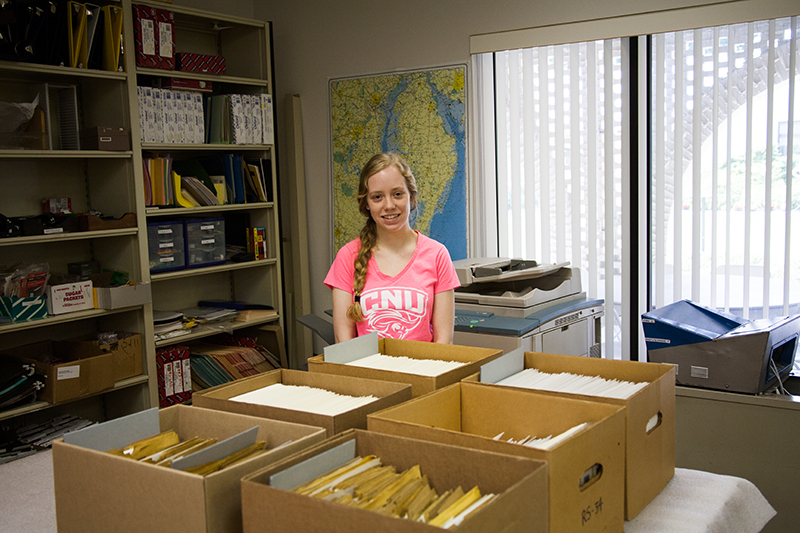 Melissa standing in front of the boxes of photographs