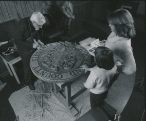 Otis Stephens demonstrating woodcarving to two guests, 1980