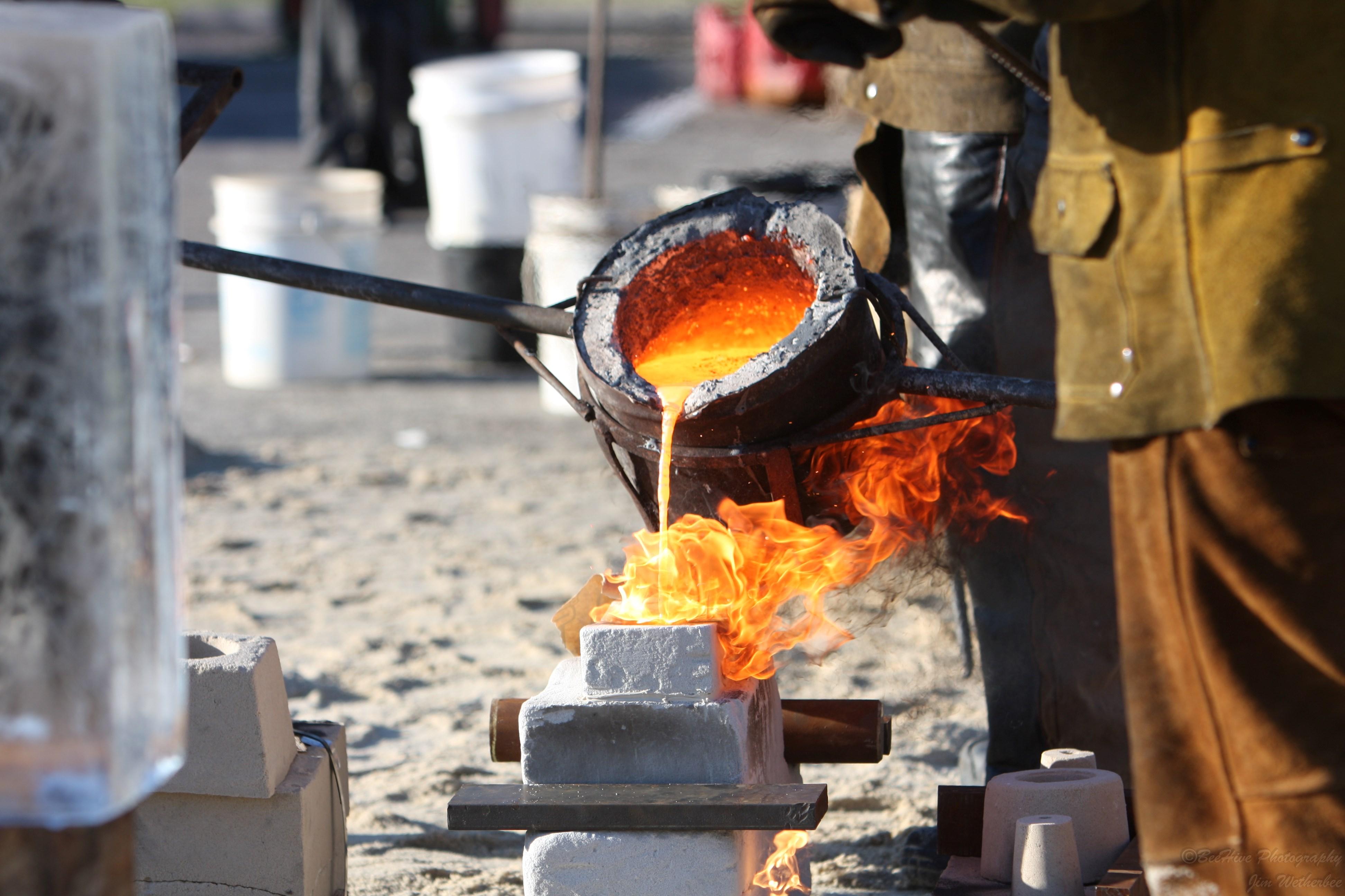 Pouring iron into a mold.
