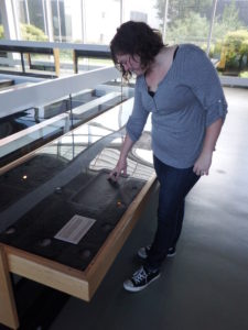 Conservator Laurie examining a deck plate from the Monitor. This artifact is safe for visitors to touch.