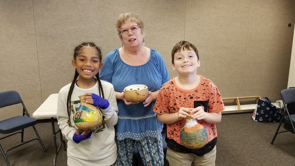 Three people with gourd drums