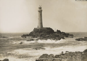 View of a lighthouse perched on a small outcropping.