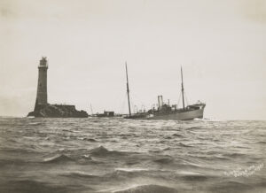 Partial view of a sinking ship next to a lighthouse on a small outcropping.