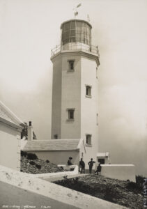 Looking at the sidewalk approach to a lighthouse.