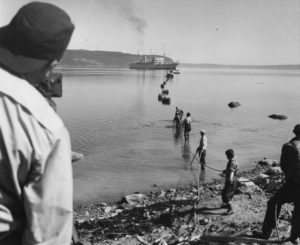 Workers on the shoreline feeding the transatlantic telephone cable into the water. The cable ship Monarch is in the background.